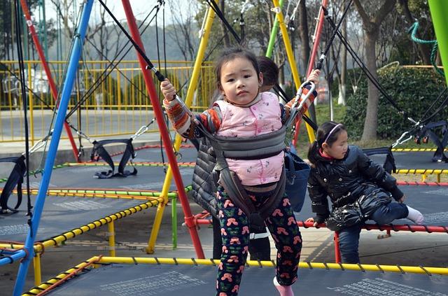 dítě připevněné a skákající na trampolíně
