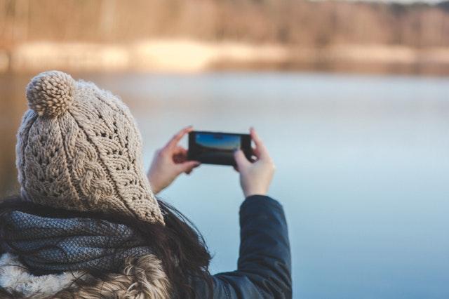 Malá dívka fotografující mobilem krajinu