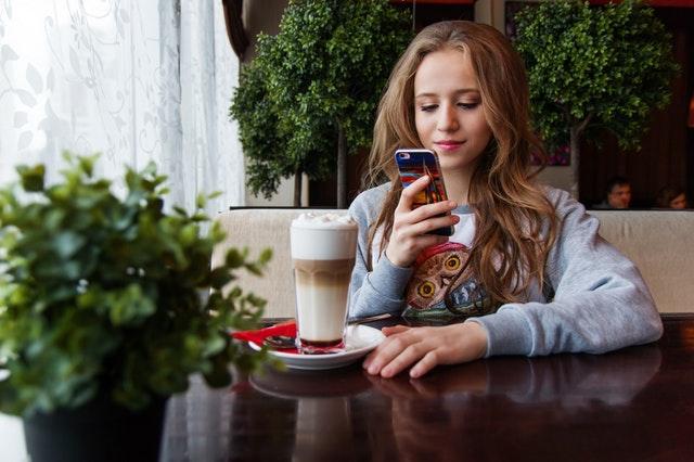 Dívka sedící u stolu s kávou a mobilem v ruce