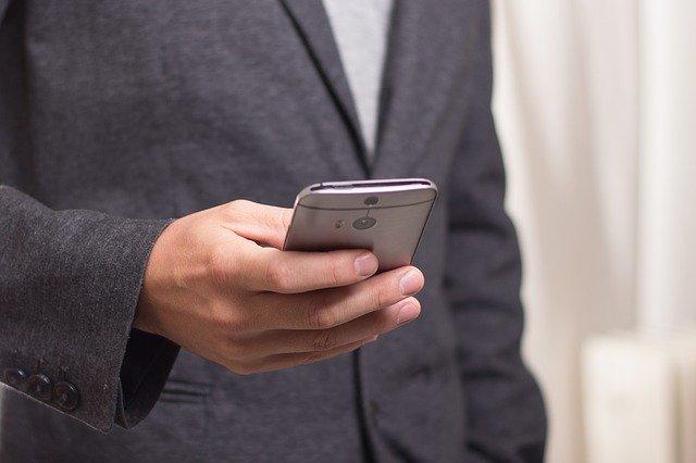 muž hledající v telefonu kontaktní informace